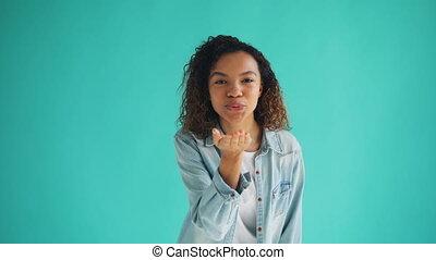 Portrait of charming African American girl sending air kiss...