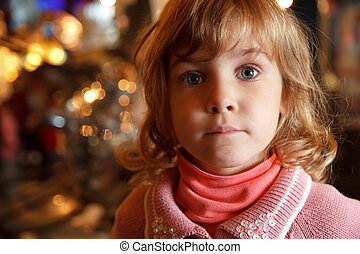 Portrait of charming little girl in background lights. Close-up. Indoors.
