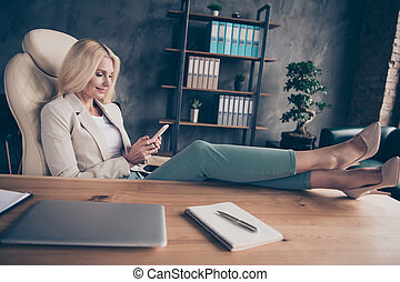 Portrait of charming middle aged blonde hair woman use cellphone have chat with her workforce career partners type messages sit in chair put her high-heels on wooden table