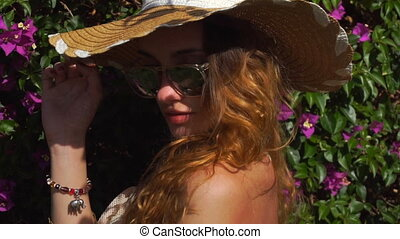 young blonde girl in sunglasses and straw hat posing in the blooming garden