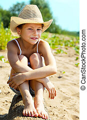 Portrait of charming young girl sitting on log