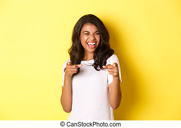 Portrait of cheeky, beautiful african-american woman in white t-shirt, winking and pointing fingers at camera to say congrats, praising you, standing over yellow background