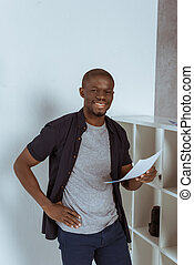 portrait of cheerful african american man with papers in hand