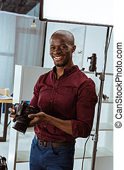portrait of cheerful african american photographer with photo camera in hands looking at camera in studio