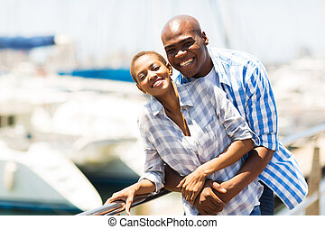 cheerful african couple at the harbor