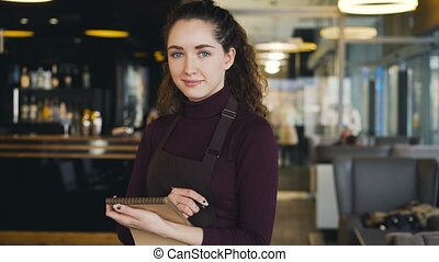 Portrait of cheerful and beautiful young waitress standing,...