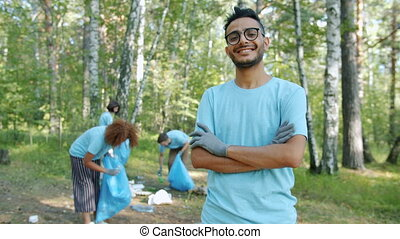 Portrait of cheerful Arabian man volunteer in uniform smiling in polluted forest