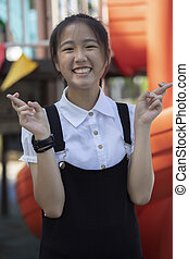 portrait of cheerful asian teenager in playground