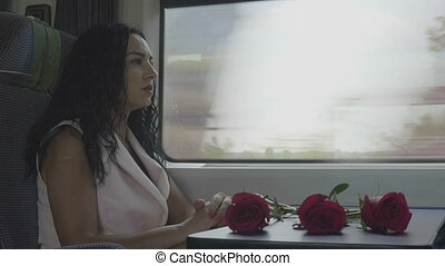 Portrait of cheerful attractive woman going on vacation sitting next the train window having conversation and smiling with roses as present during the journey