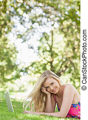 Portrait of cheerful attractive woman lying on a lawn using her notebook smiling at camera
