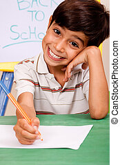 Portrait of cheerful boy writing notes