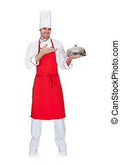 Portrait of cheerful chef presenting silver tray