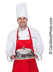 Portrait of cheerful chef with silver tray
