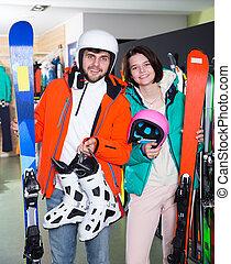 couple buying in full skiing gear