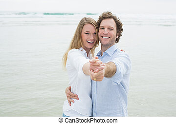 Portrait of cheerful couple dancing at beach