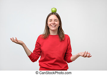 portrait of cheerful european woman with apple on her head, over white background