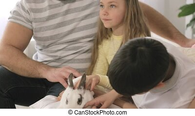 Portrait of cheerful family that is stroking a rabbit while sitting on the sofa