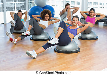 Portrait of cheerful fitness class doing pilates exercise in...