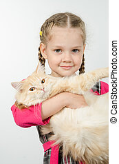 Portrait of cheerful four-year girl with a cat in her arms