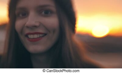 Portrait of cheerful girl smiling with red lips at sunset,...