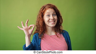 Portrait of cheerful girl student showing OK gesture smiling...