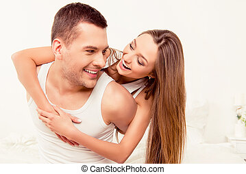 Portrait of cheerful happy man piggybacking his wife