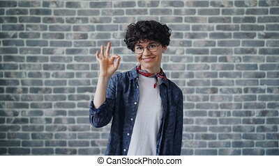 Portrait of cheerful hipster showing OK hand gesture smiling...