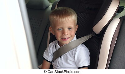 Portrait of cheerful laughing boy in a children's car seat during a summer trip.