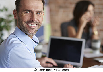 Portrait of cheerful man in front of computer