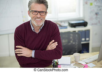 Portrait of cheerful man sitting on the desk