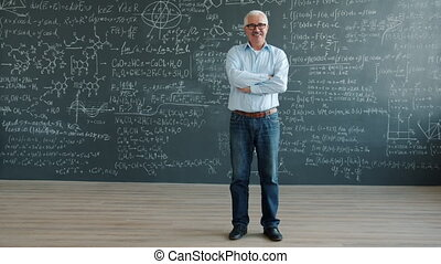 Portrait of cheerful man standing in class with chalkboard wall smiling looking at camera