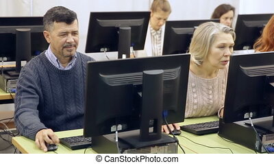 Portrait of cheerful modern elderly people working on computer with young female teacher during pc class