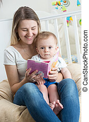 Portrait of cheerful mother reading book to her baby boy at living room