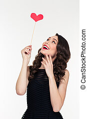 Portrait of cheerful retro styled young woman with heart ...