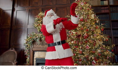 Portrait of cheerful Santa Claus having fun dancing in decorated house wearing red costume