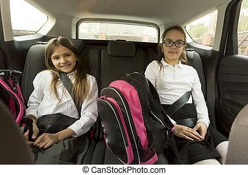 Portrait of cheerful schoolgirls sitting on car back seat