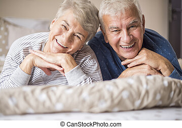 Portrait of cheerful senior adults in the bedroom