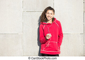Portrait of cheerful sportswoman using mobile phone