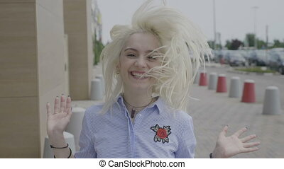 Portrait of cheerful teenage woman laughing and jumping up...
