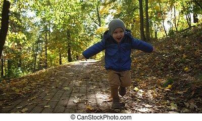 Portrait of cheerful toddler boy running in park