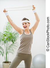 Portrait of cheerful woman in sportswear with towel
