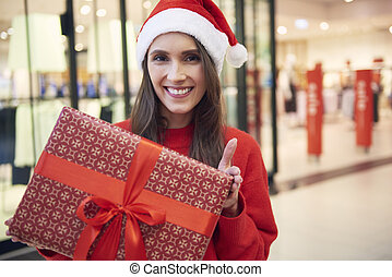 Portrait of cheerful woman with christmas present