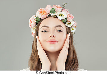 Portrait of cheerful woman with healthy skin and flowers wreath on white background
