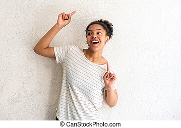 cheerful young african american girl dancing by white wall with arms raised