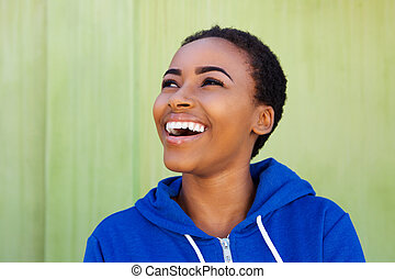 african american woman laughing against green background