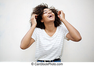 cheerful young african american woman laughing and looking up