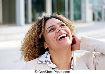 cheerful young african american woman laughing outside