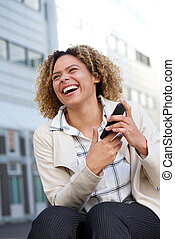 cheerful young african american woman laughing outside with cellphone