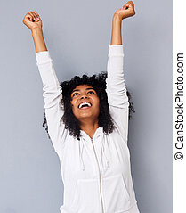 cheerful young african american woman laughing with arms raised against gray background