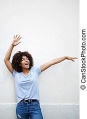 cheerful young african american woman laughing with arms raised
